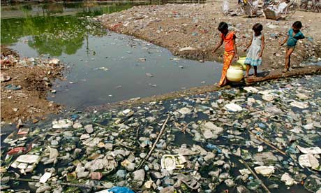 Children carry drinking water as they pass through a polluted pond in Allahabad,