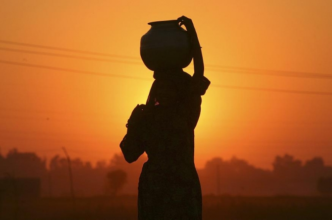 A Gujjar or nomad woman carrying a pitcher filled with drinking water is silhoue