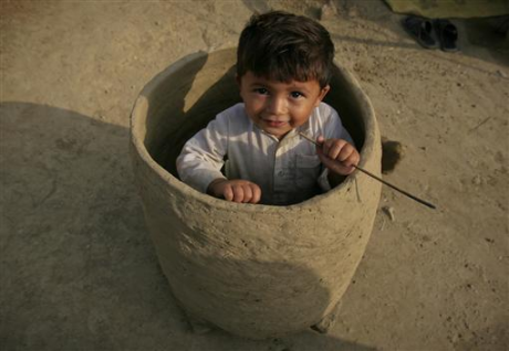 An internally displaced child sits in a mud oven outside his family tent at a ca