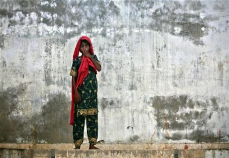 Zahida, a nine-year-old girl displaced by floods stands amidst a wall with rainw