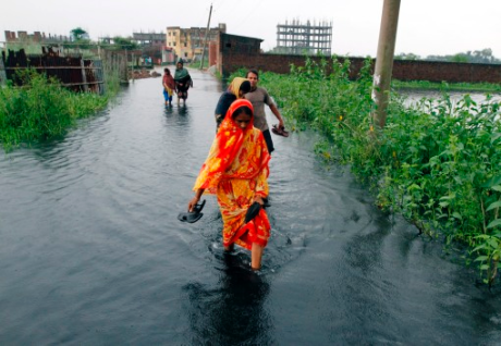 eople wade through knee-deep water on the outskirts of Dhaka, Aug. 10, 2011. REU